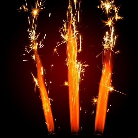 three firework sparklers with red glowing photo