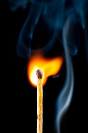 igniting match with smoke, black background photo