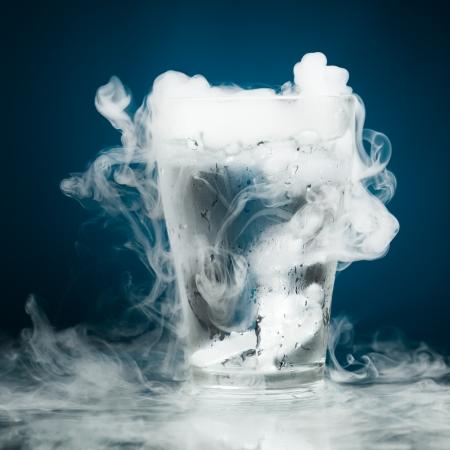 glas water met ijs damp, blauwe achtergrond