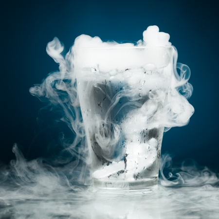 vapor: glass of water with ice vapor, blue background Stock Photo