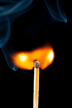 igniting: igniting match with smoke, black background
