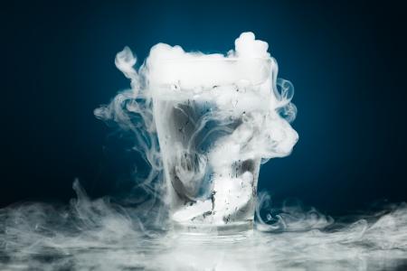 vapore acqueo: bicchiere d'acqua con ghiaccio al vapore, sfondo blu