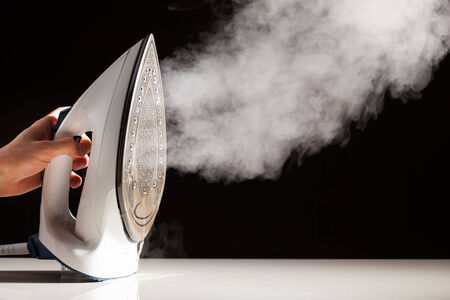 Steam iron: steam generator iron on black background Stock Photo