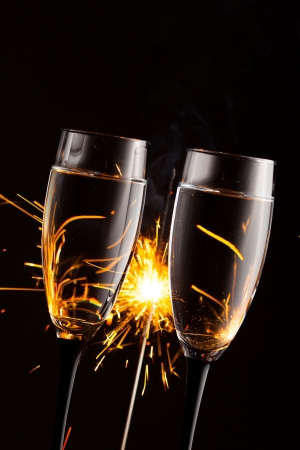 champagne glasses against christmas sparkler background photo