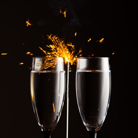 champagne glasses against christmas sparkler  photo
