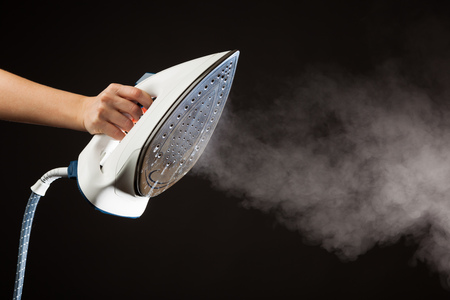 Steam iron: hand holding steam generator iron