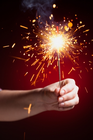 sparkler in hand, close-up view, red background photo