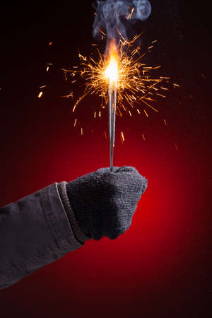 sparkler in hand mitten, close-up view, red background photo