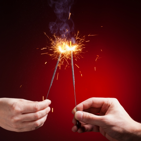 sparklers in hands, close-up view, red background photo