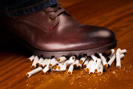 trample: shoes trampling down on cigarettes - give up smoking concept Stock Photo
