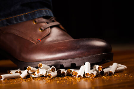 shoes off: shoes trampling down on cigarettes - give up smoking concept Stock Photo