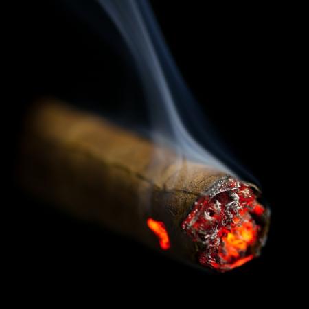 brennende Zigarre auf schwarzem Hintergrund Standard-Bild