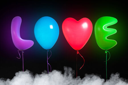 love text shaped color balloons, black background with smoke photo