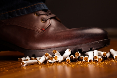 anti tobacco: shoes trampling down on cigarettes - give up smoking concept Stock Photo