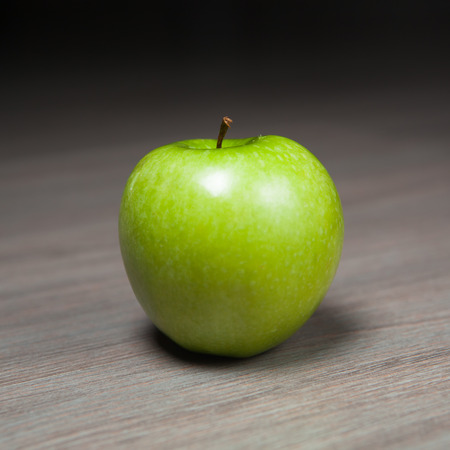 granny smith: granny smith green apple against wooden background