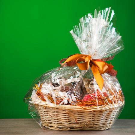 giftbasket: gift mand tegen een groene achtergrond Stockfoto