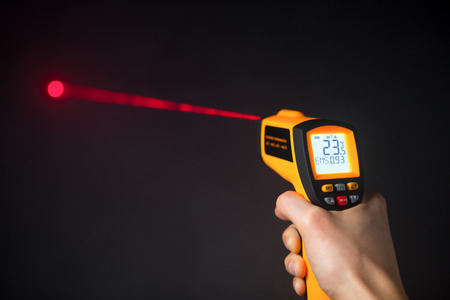 infrared laser thermometer in hand Stock Photo