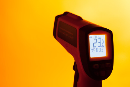 infra red: infrared laser thermometer against orange background Stock Photo