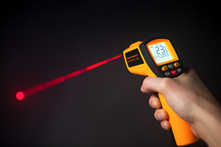 digital thermometer: infrared laser thermometer in hand Stock Photo