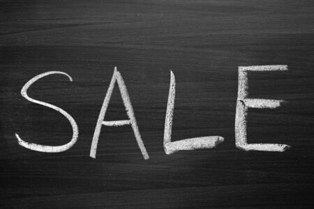 sale title written with a chalk on the blackboard photo