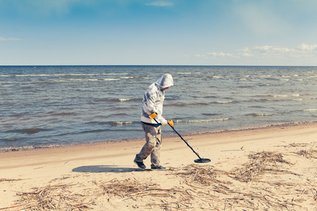 metal detector: man searching for a precious metal using a metal detector Stock Photo