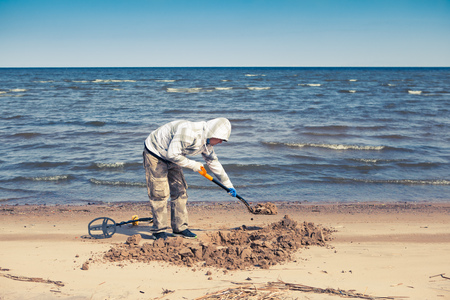 metal detector: man digging a hole to pick up a treasure