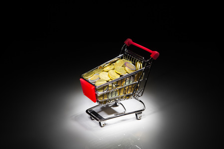shopping cart full of money on dark background photo