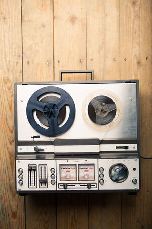 tape cassette: reel to reel tape player and recorder on wooden background