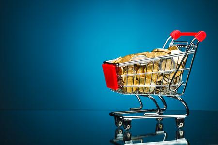 full shopping cart: shopping cart full of money on blue background Stock Photo