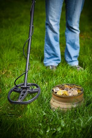 metal detector: pot of golden coins collected with help of metal detector, green grass background