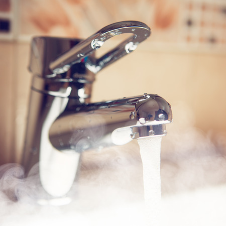 agua grifo: grifo de agua con vapor de agua caliente Foto de archivo