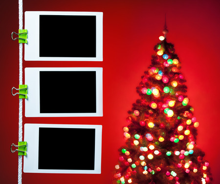 blank photos hanging on rope, christmas tree background Stock Photo