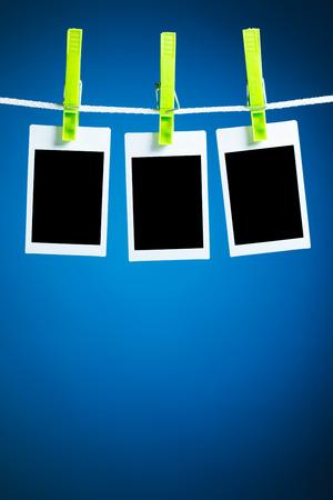 darkroom: blank photos hanging on rope, blue background