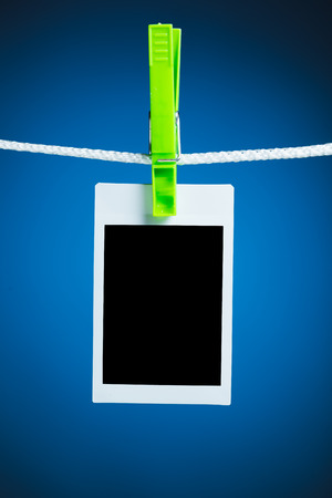 blank photo hanging on rope, blue background photo