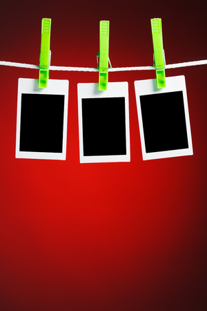 blank photos hanging on rope, red background photo
