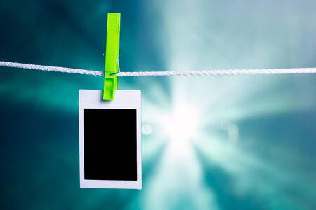 blank photo hanging on rope, blue lights background photo
