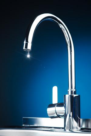 mengkraan met water drop, blauwe achtergrond Stockfoto