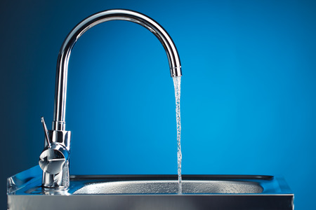 mixer tap with flowing water, blue background Standard-Bild