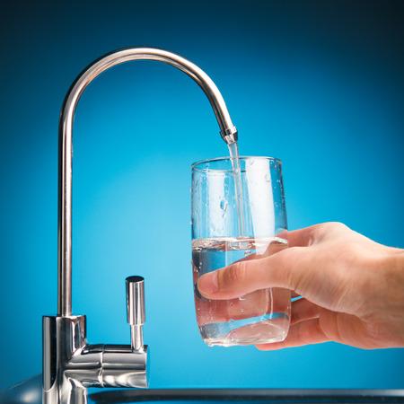 agua: mano vertiendo un vaso de agua del grifo de filtro, fondo azul