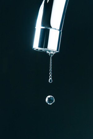 water drop on faucet, macro view Banco de Imagens