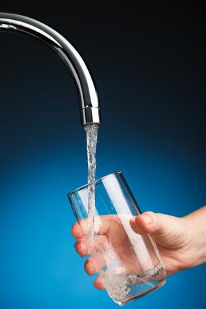 tomando agua: verter la mano un vaso de agua del grifo filtro