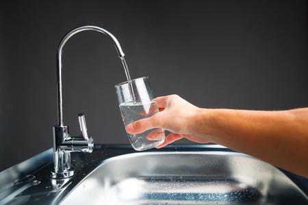 hand gieten van een glas water uit filter kraan Stockfoto