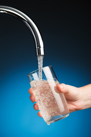 Hand gießt ein Glas Wasser aus Filter-Tap- Standard-Bild - 34862234
