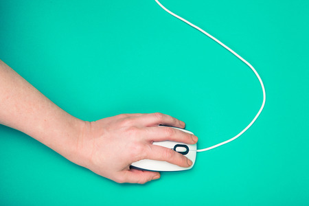 white mouse: hand on computer mouse, emerald background Stock Photo