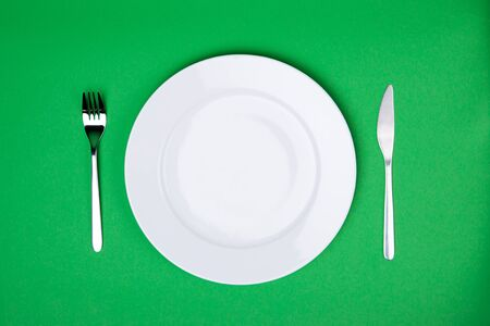 place setting: place setting with white plate, fork and knife on green background