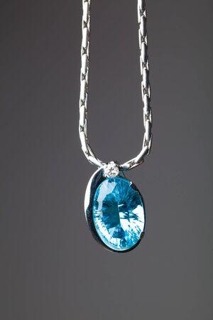 sapphire: azul colgante de zafiro sobre fondo gris Foto de archivo