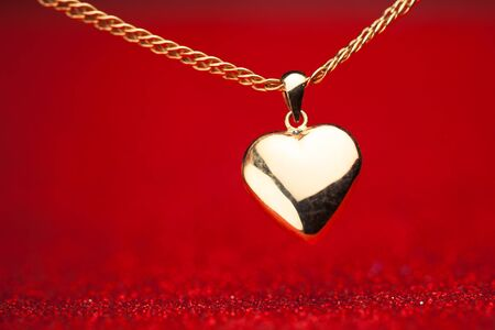 gold heart pendant on red background Stock Photo