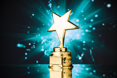 star award: gold star trophy against blue sparks background Stock Photo