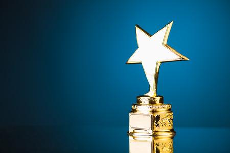 premios: trofeo de la estrella de oro sobre fondo azul Foto de archivo