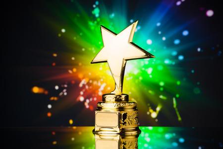 gold star trophy against rainbow sparks background Foto de archivo